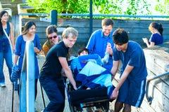 Garçon handicapé dans le fauteuil roulant étant soulevé vers le haut des escaliers par la famille Photographie stock