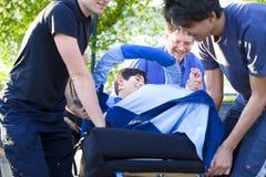 Garçon handicapé dans le fauteuil roulant étant soulevé vers le haut des escaliers par la famille Image libre de droits