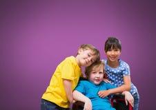 Garçon handicapé dans le fauteuil roulant avec des amis avec le fond pourpre Photo stock