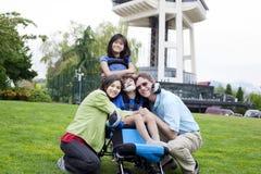 Garçon handicapé dans le fauteuil roulant entouré par la famille Photographie stock