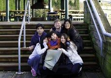 Garçon handicapé environnant de famille interraciale dans l'outdoo de fauteuil roulant Photo libre de droits