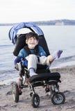 Garçon handicapé heureux dans le fauteuil roulant sur la plage Photo libre de droits