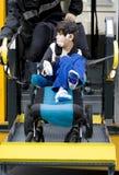 Garçon handicapé sur l'ascenseur de fauteuil roulant d'autobus scolaire Photo libre de droits