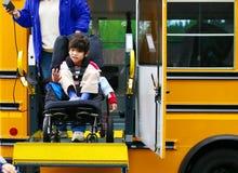 Garçon handicapé sur le levage de fauteuil roulant de bus Photographie stock libre de droits