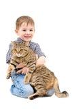 Garçon heureux étreignant un droit écossais de chat Photo stock