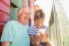 Garçon heureux avec le grand-père à l'aide du téléphone intelligent tout en se reposant par le mur Photo libre de droits
