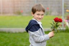 Garçon heureux avec un bouquet des roses Image stock