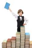 Garçon heureux avec un livre à la grande pile de livres Photographie stock libre de droits