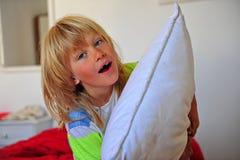 Garçon heureux avec un oreiller dans la chambre dans le matin image stock