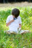 Garçon heureux avec une loupe et un livre photo stock