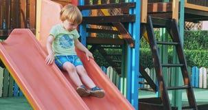Garçon heureux ayant l'amusement dans le parc d'attractions d'enfants clips vidéos