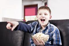 Garçon heureux blond regardant la TV et mangeant du maïs éclaté Photos libres de droits