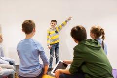 Garçon heureux d'étudiant montrant quelque chose au mur blanc Images stock