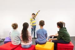 Garçon heureux d'étudiant montrant quelque chose au mur blanc Images libres de droits