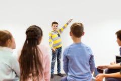 Garçon heureux d'étudiant montrant quelque chose au mur blanc Photos stock