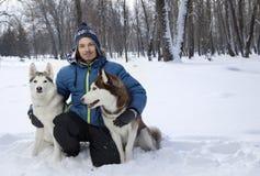 Garçon heureux d'adolescent de Noël jouant avec le chien enroué blanc dans le jour d'hiver, le chien et l'enfant sur la neige Images libres de droits