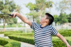 Garçon heureux d'Asiang jouant le badminton images libres de droits