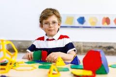 Garçon heureux d'enfant avec des verres ayant l'amusement avec le bâtiment et créant les chiffres géométriques, apprenant des mat Images libres de droits