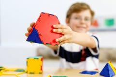 Garçon heureux d'enfant avec des verres ayant l'amusement avec le bâtiment et créant les chiffres géométriques, apprenant des mat Image libre de droits