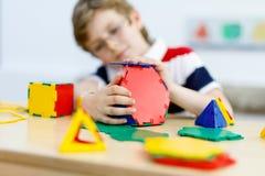 Garçon heureux d'enfant avec des verres ayant l'amusement avec le bâtiment et créant les chiffres géométriques, apprenant des mat Images stock