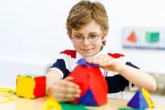 Garçon heureux d'enfant avec des verres ayant l'amusement avec le bâtiment et créant les chiffres géométriques, apprenant des mat Photographie stock
