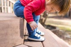 Garçon heureux d'enfant en bas âge attachant ses espadrilles Images stock