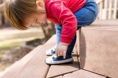 Garçon heureux d'enfant en bas âge attachant ses espadrilles Photo libre de droits