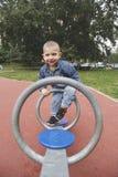 Garçon heureux d'enfant jouant seesawing dans le terrain de jeu au parc Photos libres de droits