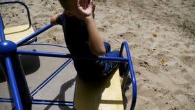 Garçon heureux d'enfant tournant sur le carrousel au terrain de jeu dans le mouvement lent banque de vidéos