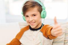 Garçon heureux dans des écouteurs montrant des pouces à la maison Photos stock