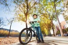Garçon heureux dans le casque tenant le vélo Images stock