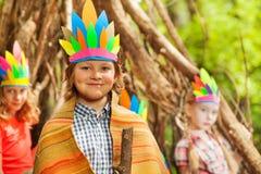 Garçon heureux dans le costume du ` s d'Injun jouant avec des amis Images libres de droits