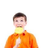 Garçon heureux dans le T-shirt orange avec la sucrerie colorée Photos stock