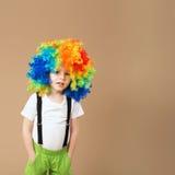 Garçon heureux de clown avec la grande perruque colorée Image stock
