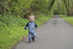 Garçon heureux de deux ans jouant et courant dehors Photos stock