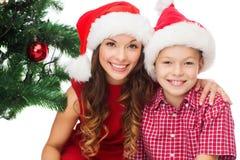 Garçon heureux de mère et d'enfant dans des chapeaux d'aide de Santa Images libres de droits