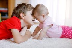 Garçon heureux de petit enfant avec le bébé nouveau-né, soeur mignonne siblings Frère et bébé jouant ensemble Images stock