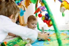 Garçon heureux de petit enfant avec le bébé nouveau-né, soeur mignonne siblings Frère et bébé jouant ensemble Photos stock