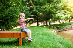 Garçon heureux de sourire s'asseyant sur le banc près du lac L'heure d'été weeken Photo libre de droits