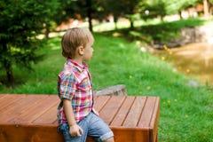 Garçon heureux de sourire s'asseyant sur le banc près du lac L'heure d'été weeken Photographie stock libre de droits