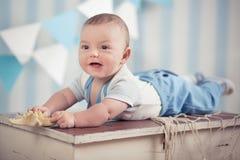 Garçon heureux drôle beau d'enfant de bébé posant sur la table en bois de fourrure dans le studio bleu Photo stock