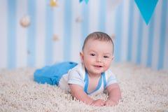 Garçon heureux drôle beau d'enfant de bébé posant sur la table en bois de fourrure dans le studio bleu Images stock