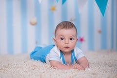 Garçon heureux drôle beau d'enfant de bébé posant sur la table en bois de fourrure dans le studio bleu Photos stock
