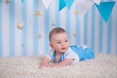 Garçon heureux drôle beau d'enfant de bébé posant sur la table en bois de fourrure dans le studio bleu Photographie stock