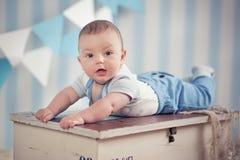 Garçon heureux drôle beau d'enfant de bébé posant sur la table en bois de fourrure dans le studio bleu Image libre de droits