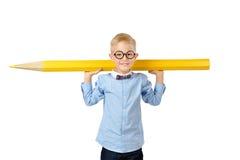 Garçon heureux en verres et bowtie posant avec un crayon énorme Concept éducatif D'isolement au-dessus du blanc photos stock
