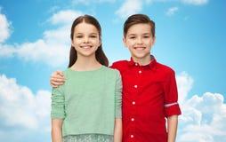 Garçon heureux et fille étreignant au-dessus du ciel bleu Photos stock