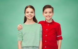Garçon heureux et fille étreignant au-dessus du panneau de craie vert Photos stock