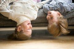Garçon heureux et fille ayant le mensonge d'amusement ensemble à l'envers Image libre de droits