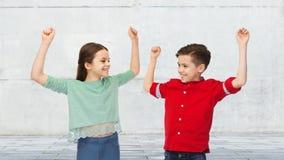 Garçon heureux et fille célébrant la victoire Photographie stock